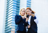 Portrait of two unhappy, dissatisfied business women reading som — Stock Photo
