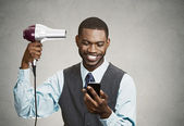 Happy executive holding smart phone while drying his hair — Stock Photo