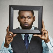 Portrait young funny executive man sticking head in picture fram — Stock Photo #50121411