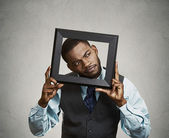 Portrait young funny executive man sticking head in picture fram — Stock Photo