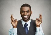 Hopeful businessman crossing his fingers — Stock Photo