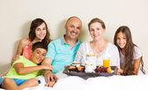 Happy family having breakfast in bed — Stock Photo