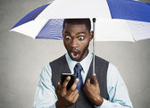 Shocked executive reading breaking news on a rainy day — Stock Photo