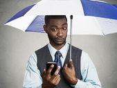 Executive man holding smart phone, reading news on a rainy day — Stock Photo