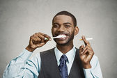Man holding cigarette and toothbrush — Stock Photo