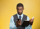 Shoked man with phone holding book — Stock Photo