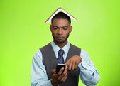 Man with book over head reading news on mobile — Stock Photo
