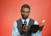Skeptical man looking at phone holding book — Stock Photo