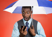 Man reading news on phone holding umbrella — Stock Photo