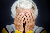 Closeup portrait depressed old woman covering her face with hand — Stock Photo