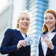 Happy business women holding credit cards and cash reward — Stock Photo #50370199