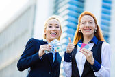 Happy business women holding credit cards and cash reward — Stock Photo