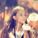 Happy girl blowing dandelion flower — Stock Photo #50955047