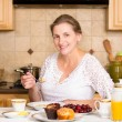 Middle aged woman having breakfast in a kitchen — Stock Photo #50955299