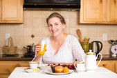 Middle aged woman having breakfast in a kitchen — Stock Photo