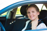 Woman pulling on seat belt inside her car — Stock Photo