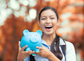 Happy woman holding piggy bank — Stock Photo