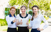 Successful business women giving thumbs up — Stock Photo