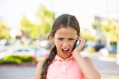 Angry child screaming on the mobile phone — Stock Photo