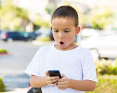 Surprised boy looking at his smart phone — Stock Photo