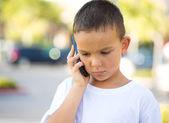 Sad boy talking on mobile phone — Stock Photo