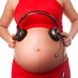 Pregnant woman with headphones close to her belly — Stock Photo