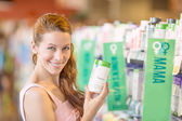 Happy woman picking daily food supplements in a store — Stock Photo