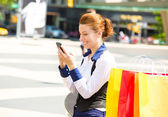 Happy shopping woman texting on a mobile phone in Manhattan NYC — Stock Photo