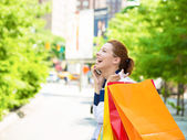 Happy shopping woman talking on a phone in Manhattan NYC — Stock Photo