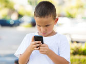 Unhappy boy looking at his smart phone — Stock Photo