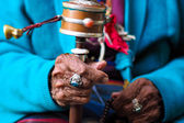 Rotation buddhist prayer wheel at old woman's hand — Stockfoto