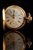 Old pocket watch on dark glass background — Stock Photo