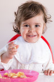 Baby girl eating fruit — Stock Photo
