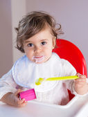 Baby girl eating yogurt with messy face — Stock fotografie