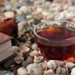Постер, плакат: Book and transparent glass cup with tea standings on shells