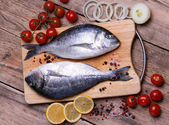 Two fresh gilt-head bream fish on cutting board with lemon, onion and tomato — Stock Photo