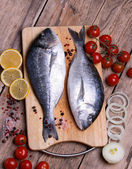 Two fresh gilt-head bream fish on cutting board with lemon,onion and cherry tomato — Stock Photo