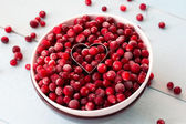 Frozen Cranberries in Bowl within heart shaped cookie cutter — Stockfoto