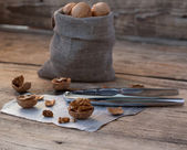 Nutcracker with walnuts on wooden background — Stock Photo