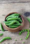 Wooden bowl full  of green peas pods. Top view. — Stock Photo