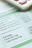 Close Up Of Pay Slip With Calculator — Stock Photo