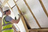 Builder Fitting Insulation Into Roof Of New Home — Stock Photo