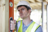 Builder Checking Work With Spirit Level — Stock Photo