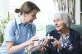 Nurse Advising Senior Woman On Medication At Home — Stock Photo