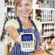 Sales Assistant In Food Store Handing Credit Card Machine To Cus — Stock Photo #49731155