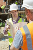 Architect Discussing Plans With Builder On Construction Site — Stock Photo