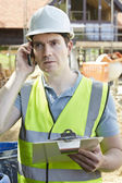 Construction Worker On Building Site Using Mobile Phone — Стоковое фото