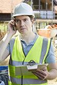 Construction Worker On Building Site Using Mobile Phone — ストック写真