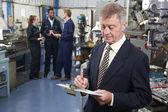 Propietario de fábrica de ingeniería con personal en segundo plano — Foto de Stock