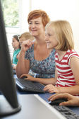 Female Elementary Pupil In Computer Class With Teacher — Stock Photo